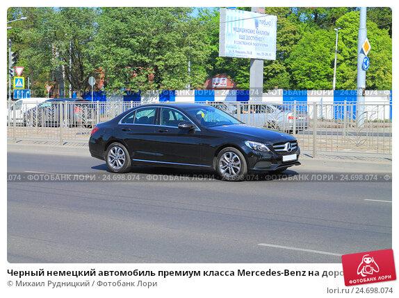 Купить «Черный немецкий автомобиль премиум класса Mercedes-Benz на дороге в солнечный день», фото № 24698074, снято 11 мая 2016 г. (c) Михаил Рудницкий / Фотобанк Лори