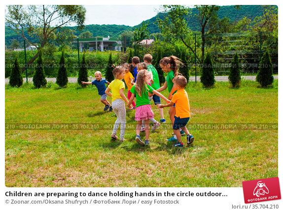 Children are preparing to dance holding hands in the circle outdoor... Стоковое фото, фотограф Zoonar.com/Oksana Shufrych / easy Fotostock / Фотобанк Лори