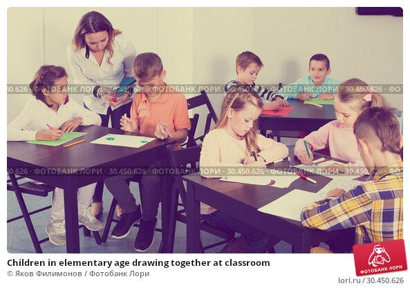 Children in elementary age drawing together at classroom. Стоковое фото, фотограф Яков Филимонов / Фотобанк Лори