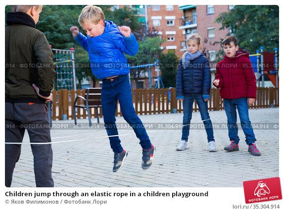 Children jump through an elastic rope in a children playground. Стоковое фото, фотограф Яков Филимонов / Фотобанк Лори
