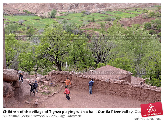 Children of the village of Tighza playing with a ball, Ounila River valley, Ouarzazate Province, region of Draa-Tafilalet, Morocco, North West Africa. (2019 год). Редакционное фото, фотограф Christian Goupi / age Fotostock / Фотобанк Лори
