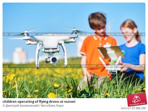 Купить «children operating of flying drone at sunset», фото № 27386330, снято 14 мая 2017 г. (c) Дмитрий Калиновский / Фотобанк Лори
