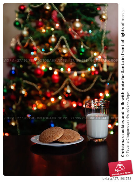 Купить «Christmas cookies and milk with note for Santa in front of lights of new year tree», фото № 27196758, снято 12 мая 2017 г. (c) Tetiana Chugunova / Фотобанк Лори