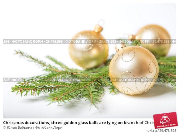 Купить «Christmas decorations, three golden glass balls are lying on branch of Christmas tree, on  white background», фото № 29478598, снято 16 ноября 2018 г. (c) Юлия Бабкина / Фотобанк Лори