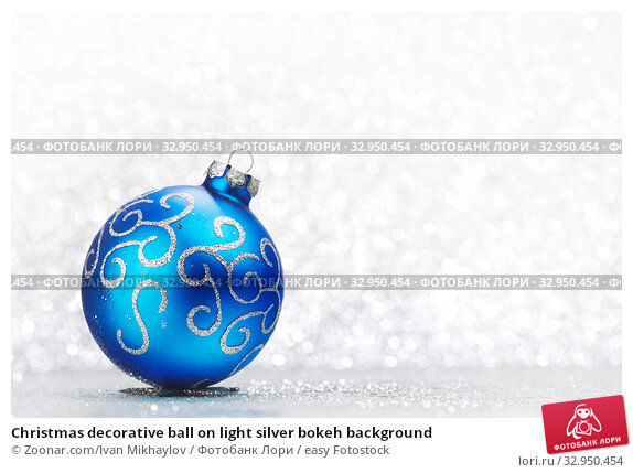 Christmas decorative ball on light silver bokeh background. Стоковое фото, фотограф Zoonar.com/Ivan Mikhaylov / easy Fotostock / Фотобанк Лори
