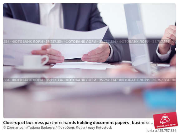 Close-up of business partners hands holding document papers , business... Стоковое фото, фотограф Zoonar.com/Tatiana Badaeva / easy Fotostock / Фотобанк Лори