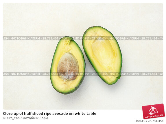 Купить «Close up of half sliced ripe avocado on white table», фото № 28731454, снято 26 апреля 2017 г. (c) Kira_Yan / Фотобанк Лори