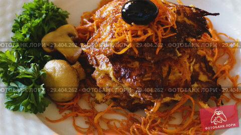 Купить «Close up of tasty fried carrot pancakes with mushrooms and greens served at plate», видеоролик № 29404262, снято 15 октября 2018 г. (c) Яков Филимонов / Фотобанк Лори