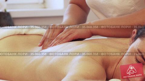 Close-up of woman relaxing during back massage lying on massage table. Стоковое видео, видеограф Алексей Кузнецов / Фотобанк Лори