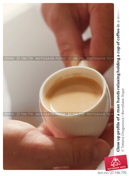 Купить «Close up profile of a man hands relaxing holding a cup of coffee in a wooden table at home with a window in the background», фото № 27196770, снято 3 июля 2017 г. (c) Tetiana Chugunova / Фотобанк Лори