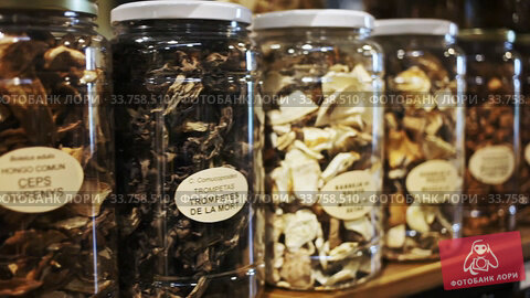 Closed glass jars with various dried mushrooms for sale on shelf in store. Стоковое видео, видеограф Яков Филимонов / Фотобанк Лори