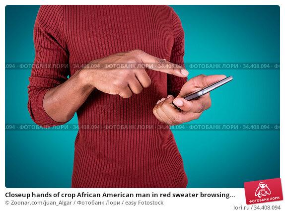 Closeup hands of crop African American man in red sweater browsing... Стоковое фото, фотограф Zoonar.com/juan_Algar / easy Fotostock / Фотобанк Лори