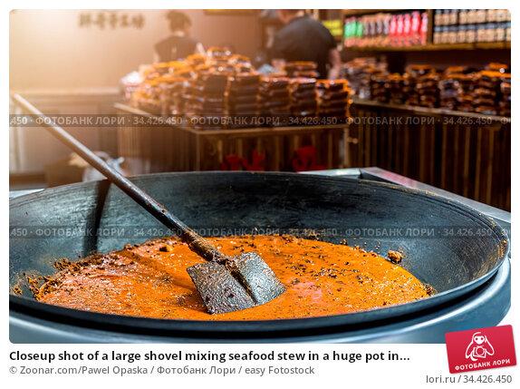 Closeup shot of a large shovel mixing seafood stew in a huge pot in... Стоковое фото, фотограф Zoonar.com/Pawel Opaska / easy Fotostock / Фотобанк Лори