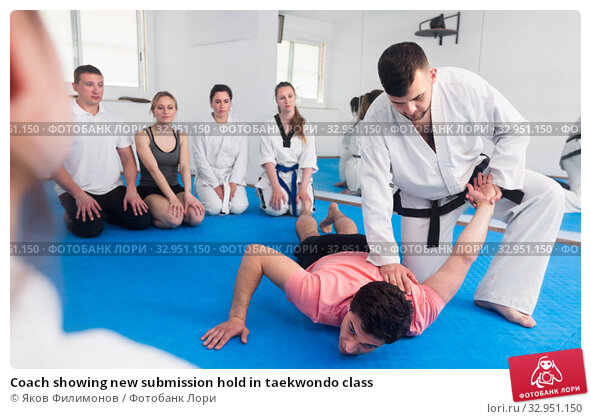 Coach showing new submission hold in taekwondo class. Стоковое фото, фотограф Яков Филимонов / Фотобанк Лори