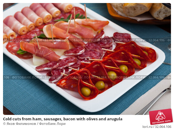 Cold cuts from ham, sausages, bacon with olives and arugula. Стоковое фото, фотограф Яков Филимонов / Фотобанк Лори
