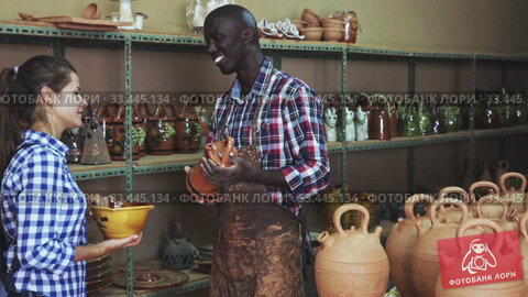Купить «Competent seller consulting young woman about purchase of handmade ceramics in pottery store», видеоролик № 33445134, снято 24 мая 2020 г. (c) Яков Филимонов / Фотобанк Лори
