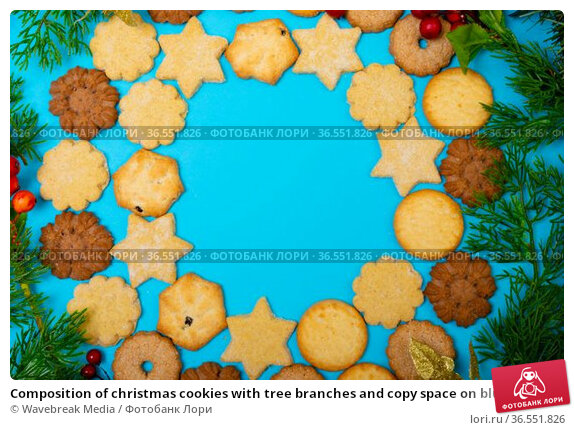 Composition of christmas cookies with tree branches and copy space on blue background. Стоковое фото, агентство Wavebreak Media / Фотобанк Лори