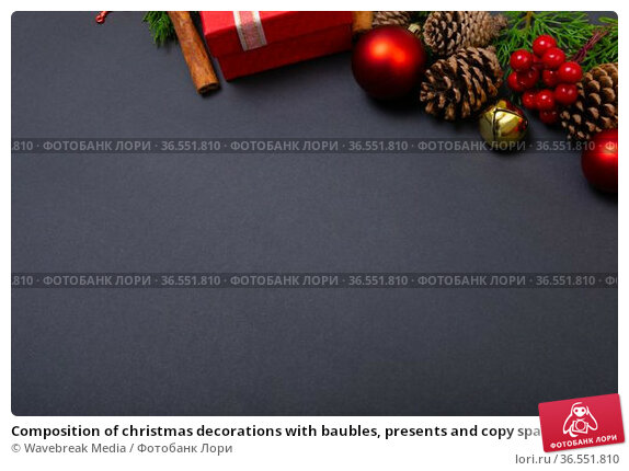 Composition of christmas decorations with baubles, presents and copy space on black background. Стоковое фото, агентство Wavebreak Media / Фотобанк Лори