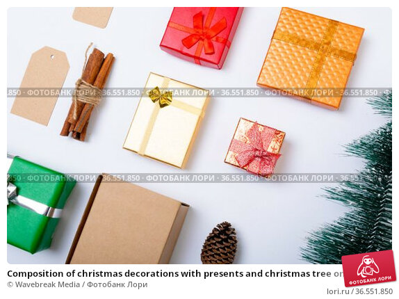 Composition of christmas decorations with presents and christmas tree on white background. Стоковое фото, агентство Wavebreak Media / Фотобанк Лори