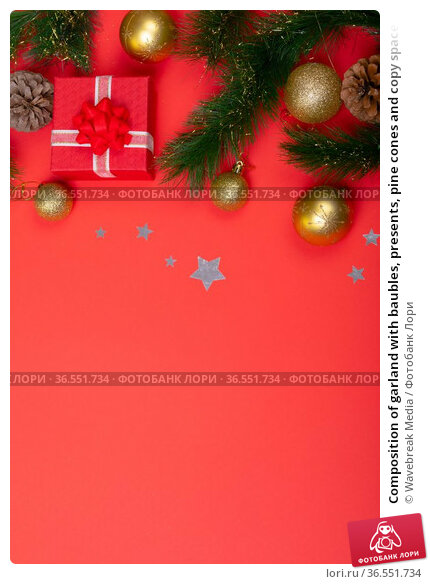 Composition of garland with baubles, presents, pine cones and copy space on red background. Стоковое фото, агентство Wavebreak Media / Фотобанк Лори