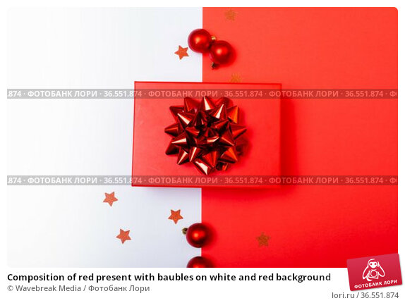 Composition of red present with baubles on white and red background. Стоковое фото, агентство Wavebreak Media / Фотобанк Лори
