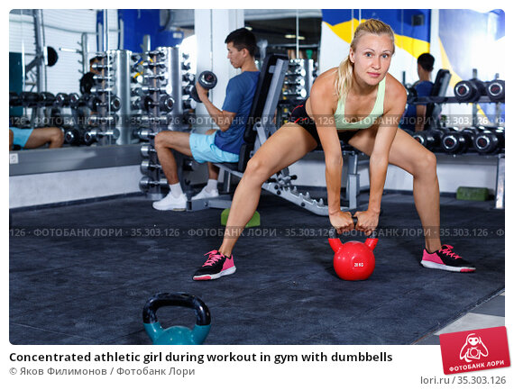 Concentrated athletic girl during workout in gym with dumbbells. Стоковое фото, фотограф Яков Филимонов / Фотобанк Лори