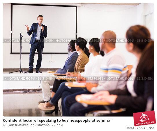Confident lecturer speaking to businesspeople at seminar. Стоковое фото, фотограф Яков Филимонов / Фотобанк Лори
