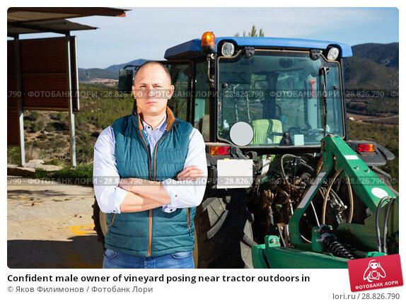 Купить «Confident male owner of vineyard posing near tractor outdoors in», фото № 28826790, снято 22 января 2018 г. (c) Яков Филимонов / Фотобанк Лори