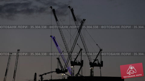 Construction cranes build the skyscraper at sunset. Стоковое видео, видеограф Алексей Кузнецов / Фотобанк Лори
