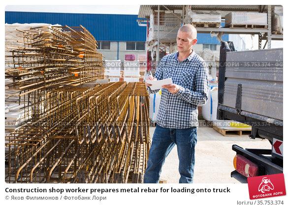 Construction shop worker prepares metal rebar for loading onto truck. Стоковое фото, фотограф Яков Филимонов / Фотобанк Лори