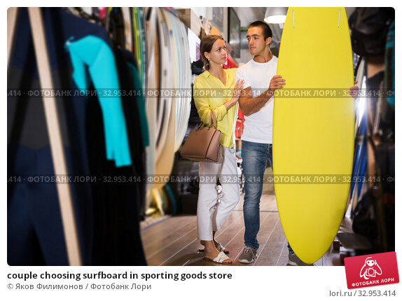 couple choosing surfboard in sporting goods store. Стоковое фото, фотограф Яков Филимонов / Фотобанк Лори