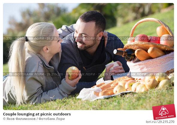 Купить «Couple lounging at picnic outdoors», фото № 29215270, снято 16 октября 2018 г. (c) Яков Филимонов / Фотобанк Лори