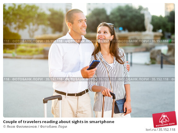 Couple of travelers reading about sights in smartphone. Стоковое фото, фотограф Яков Филимонов / Фотобанк Лори