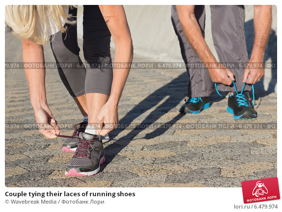 Couple tying their laces of running shoes. Стоковое фото, агентство Wavebreak Media / Фотобанк Лори