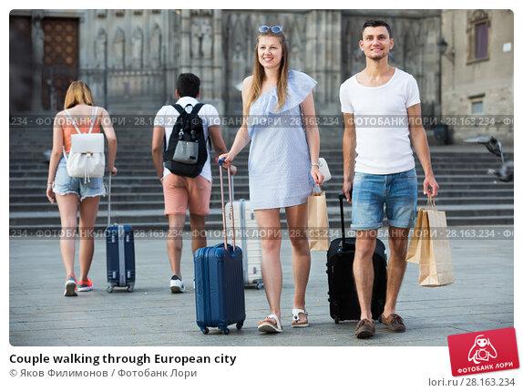 Купить «Couple walking through European city», фото № 28163234, снято 22 июня 2017 г. (c) Яков Филимонов / Фотобанк Лори
