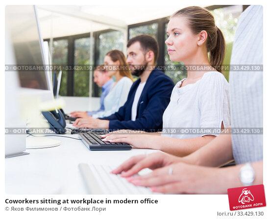 Купить «Coworkers sitting at workplace in modern office», фото № 33429130, снято 1 августа 2018 г. (c) Яков Филимонов / Фотобанк Лори