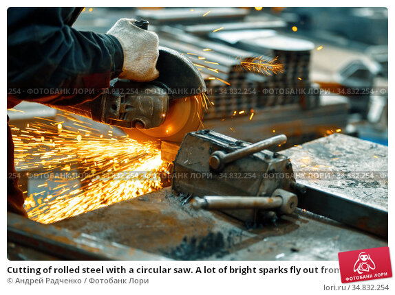 Cutting of rolled steel with a circular saw. A lot of bright sparks fly out from under the rotating disk. Стоковое фото, фотограф Андрей Радченко / Фотобанк Лори