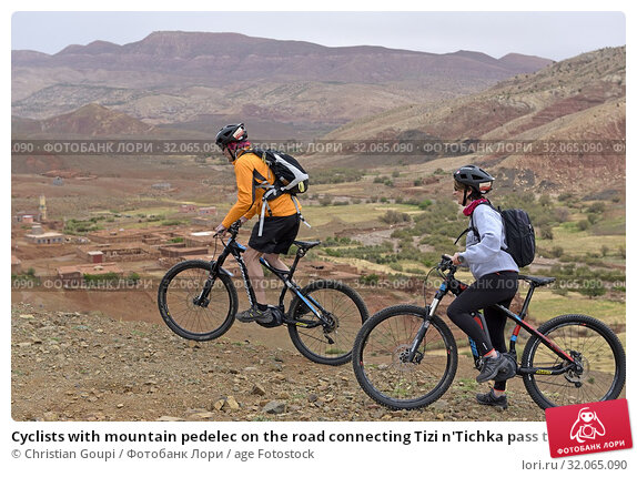 Cyclists with mountain pedelec on the road connecting Tizi n'Tichka pass to Telouet village, Ouarzazate Province, region of Draa-Tafilalet, Morocco, North West Africa. (2019 год). Редакционное фото, фотограф Christian Goupi / age Fotostock / Фотобанк Лори