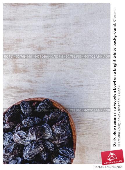 Купить «Dark blue raisins in a wooden bowl on a bright white background. Close-up. Insulated.», фото № 30769966, снято 5 декабря 2018 г. (c) Tetiana Chugunova / Фотобанк Лори