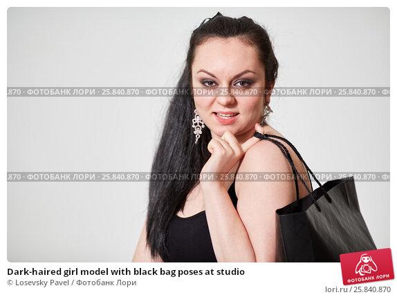Купить «Dark-haired girl model with black bag poses at studio», фото № 25840870, снято 11 января 2015 г. (c) Losevsky Pavel / Фотобанк Лори