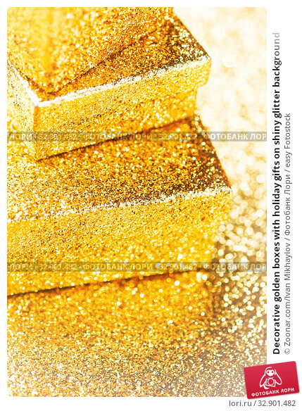 Decorative golden boxes with holiday gifts on shiny glitter background. Стоковое фото, фотограф Zoonar.com/Ivan Mikhaylov / easy Fotostock / Фотобанк Лори