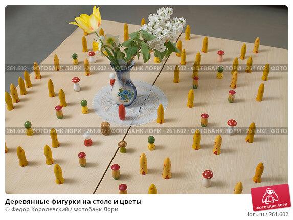Купить «Деревянные фигурки на столе и цветы», фото № 261602, снято 24 апреля 2008 г. (c) Федор Королевский / Фотобанк Лори
