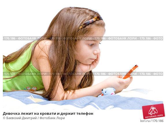 Девочка лежит на кровати и держит телефон, фото № 170186, снято 6 января 2008 г. (c) Баевский Дмитрий / Фотобанк Лори