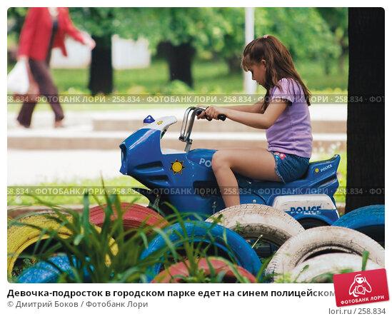 Девочка-подросток в городском парке едет на синем полицейском мотоцикле, фото № 258834, снято 28 мая 2006 г. (c) Дмитрий Боков / Фотобанк Лори
