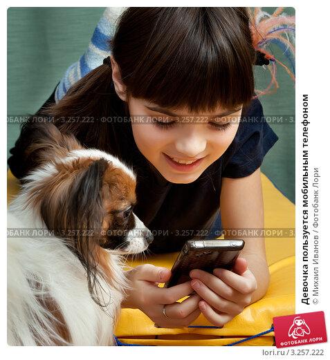 Купить «Девочка пользуется мобильным телефоном», фото № 3257222, снято 12 декабря 2017 г. (c) Михаил Иванов / Фотобанк Лори