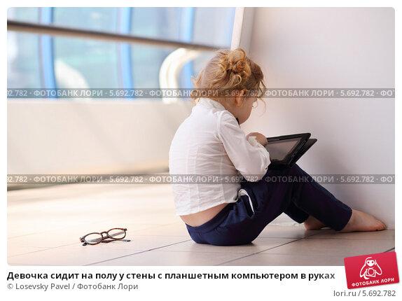 Купить «Девочка сидит на полу у стены с планшетным компьютером в руках», фото № 5692782, снято 21 июня 2013 г. (c) Losevsky Pavel / Фотобанк Лори