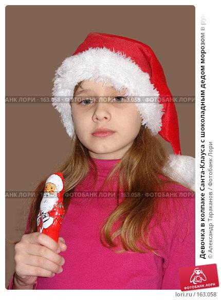 Девочка в колпаке Санта-Клауса с шоколадным дедом морозом в руках, эксклюзивное фото № 163058, снято 27 мая 2017 г. (c) Александр Тараканов / Фотобанк Лори