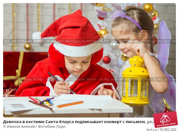 Купить «Девочка в костюме Санта-Клауса подписывает конверт с письмом, рядом стоит девочка фея с фонариком в руках», фото № 15902362, снято 12 декабря 2015 г. (c) Иванов Алексей / Фотобанк Лори