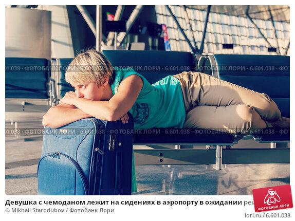 Купить «Девушка с чемоданом лежит на сидениях в аэропорту в ожидании рейса», фото № 6601038, снято 13 февраля 2019 г. (c) Mikhail Starodubov / Фотобанк Лори