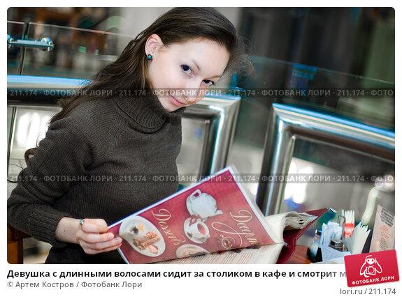 Девушка с длинными волосами сидит за столиком в кафе и смотрит меню, выбирая напиток, фото № 211174, снято 27 февраля 2008 г. (c) Артем Костров / Фотобанк Лори